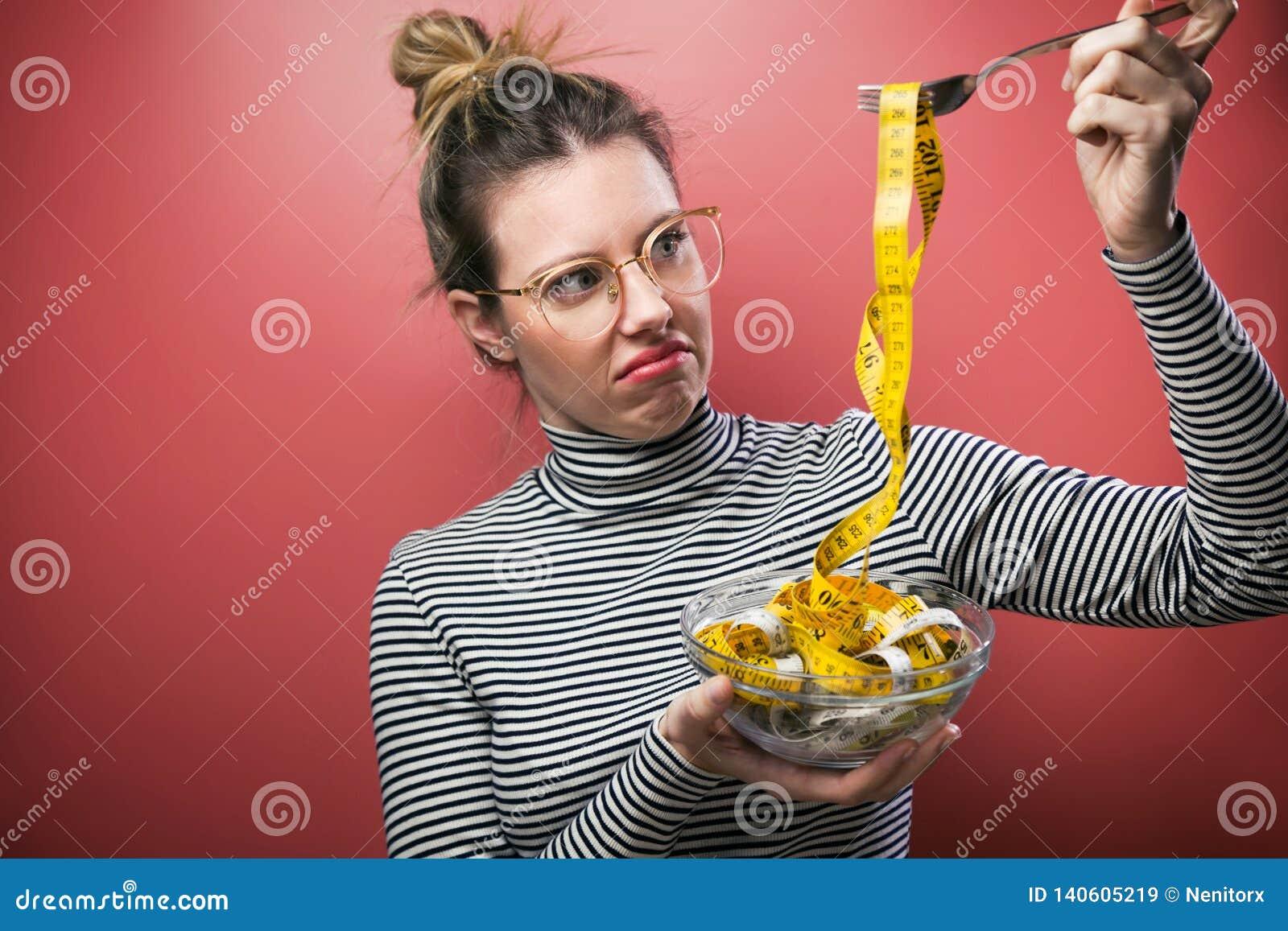 Äckla kvinnan med glasögon som rymmer bunken med att mäta band medan över rosa bakgrund