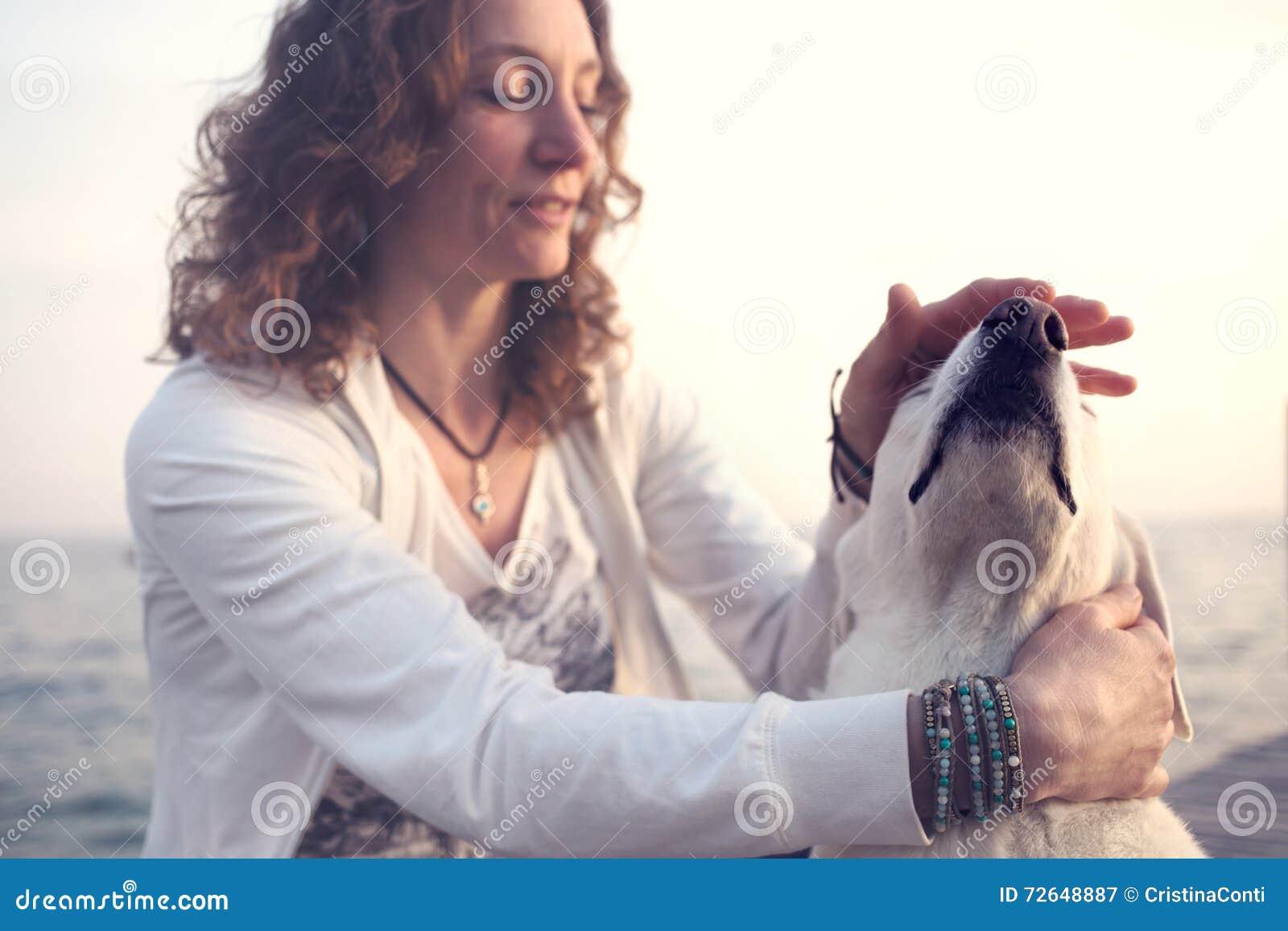 Ägare som försiktigt smeker hennes hund