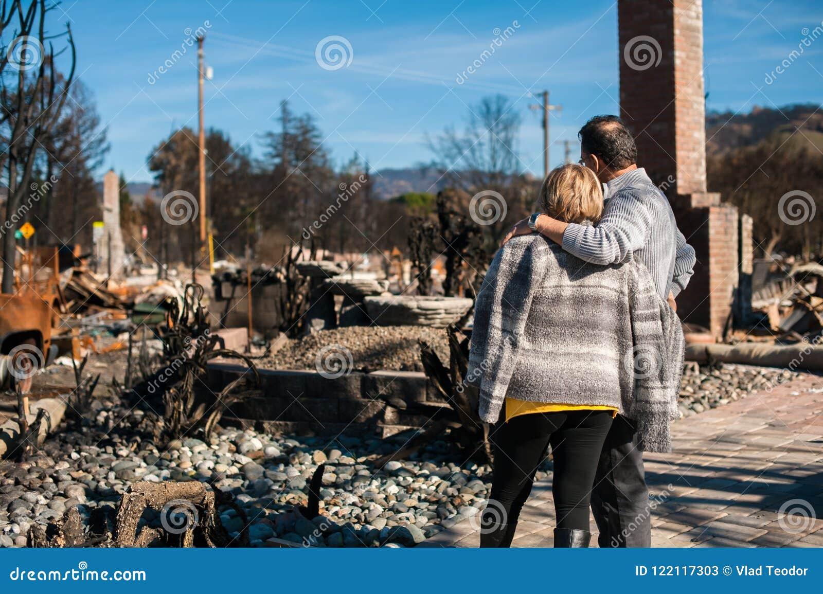 Ägare som kontrollerar det brända och fördärvade huset och gården efter brand
