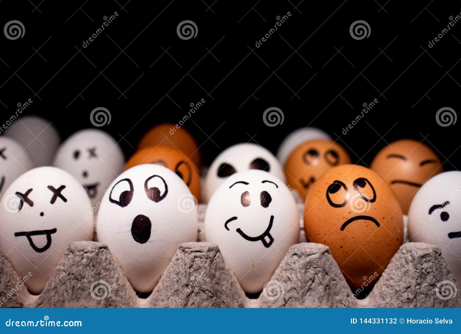 Ägg med roliga uttryck som simulerar mänskliga framsidor Begrepp av etnisk mångfald och lynnen