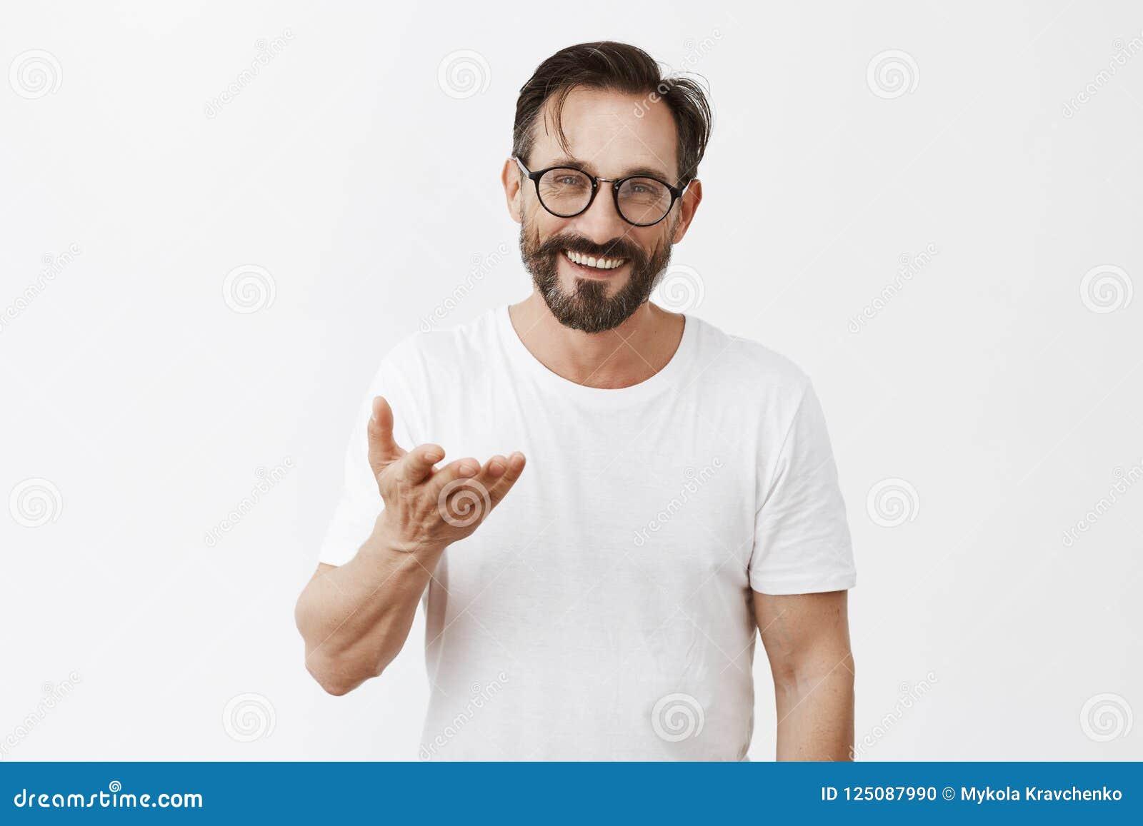 Ägna allt till dig Charmig tacksam europeisk man med skägget och stilfull frisyr i exponeringsglas som pekar med