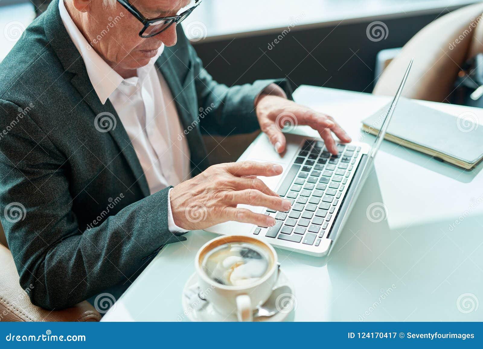 Äldre affärsman som använder bärbara datorn i kafé