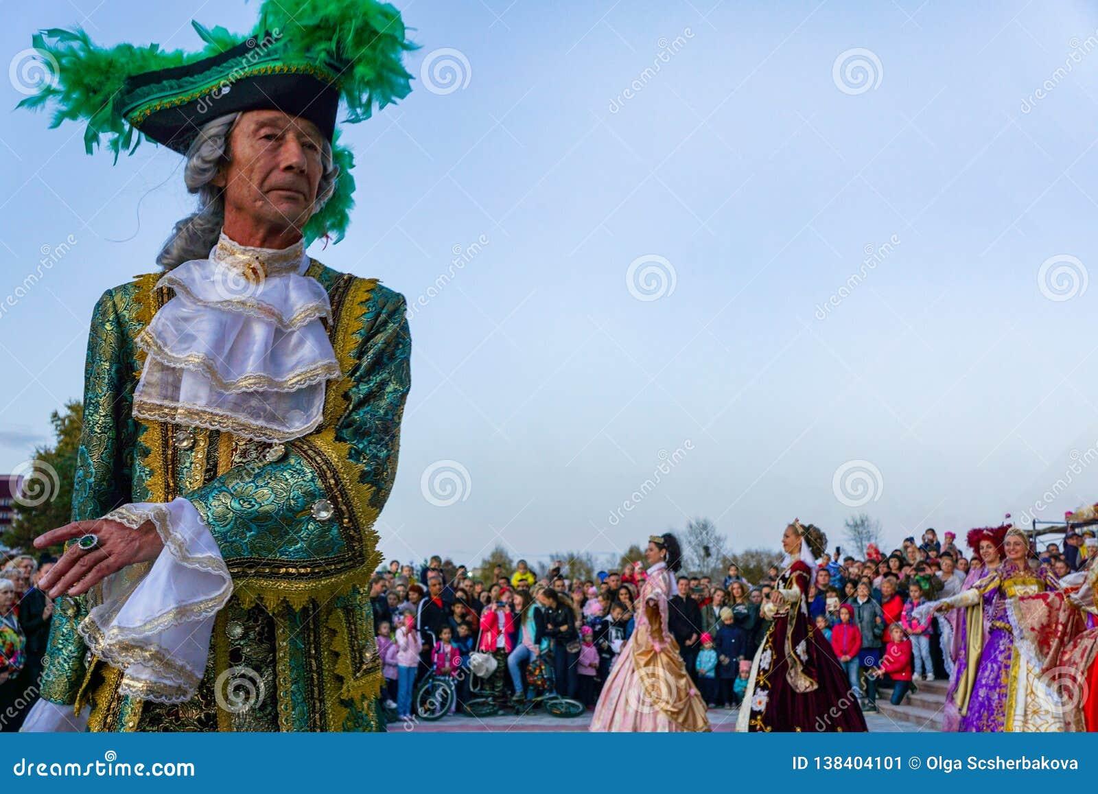 Äldre dansare i ljusa historiska medeltida dräkter som dansar i fyrkanten i sommar