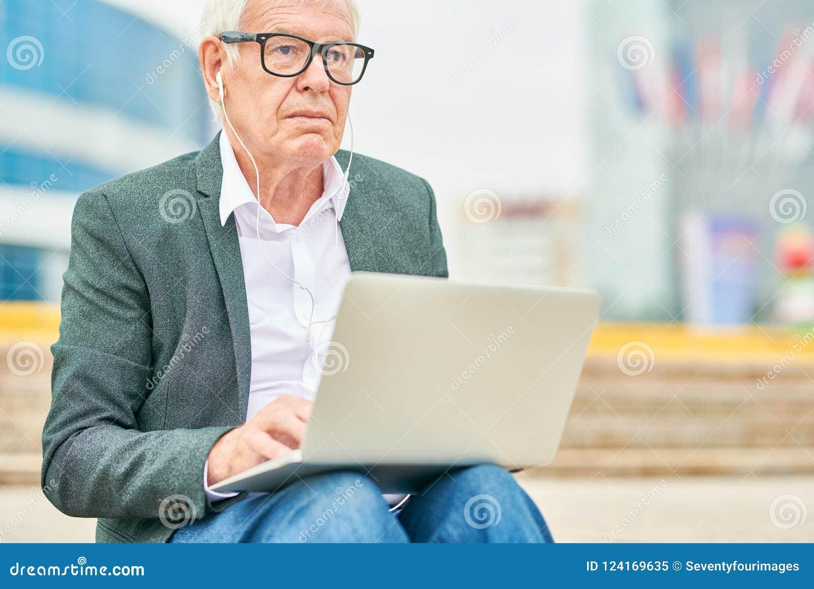 Äldre entreprenör som lyssnar till musik och använder bärbara datorn