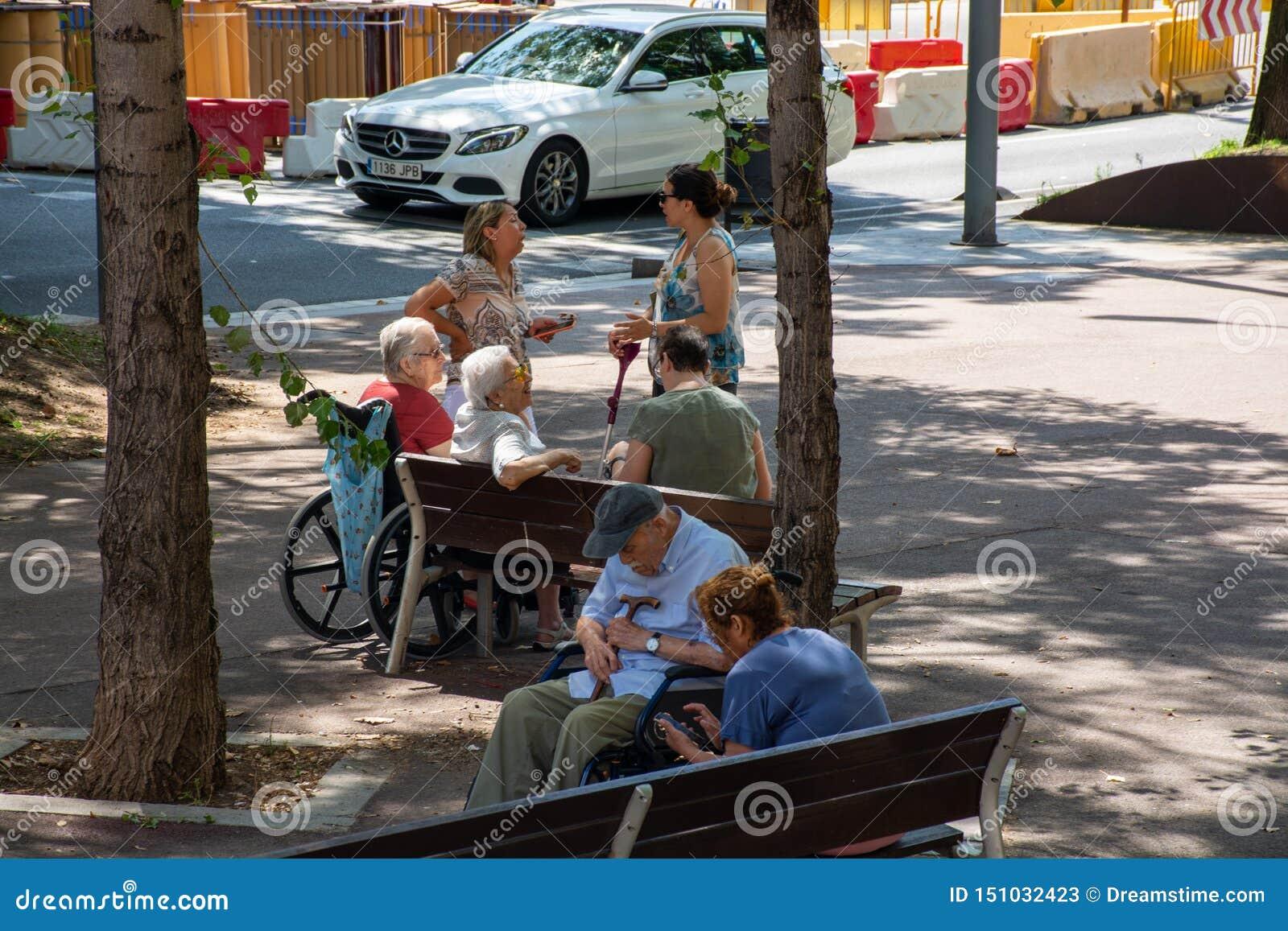 Äldre folk som sitter på bänken som sover samtal