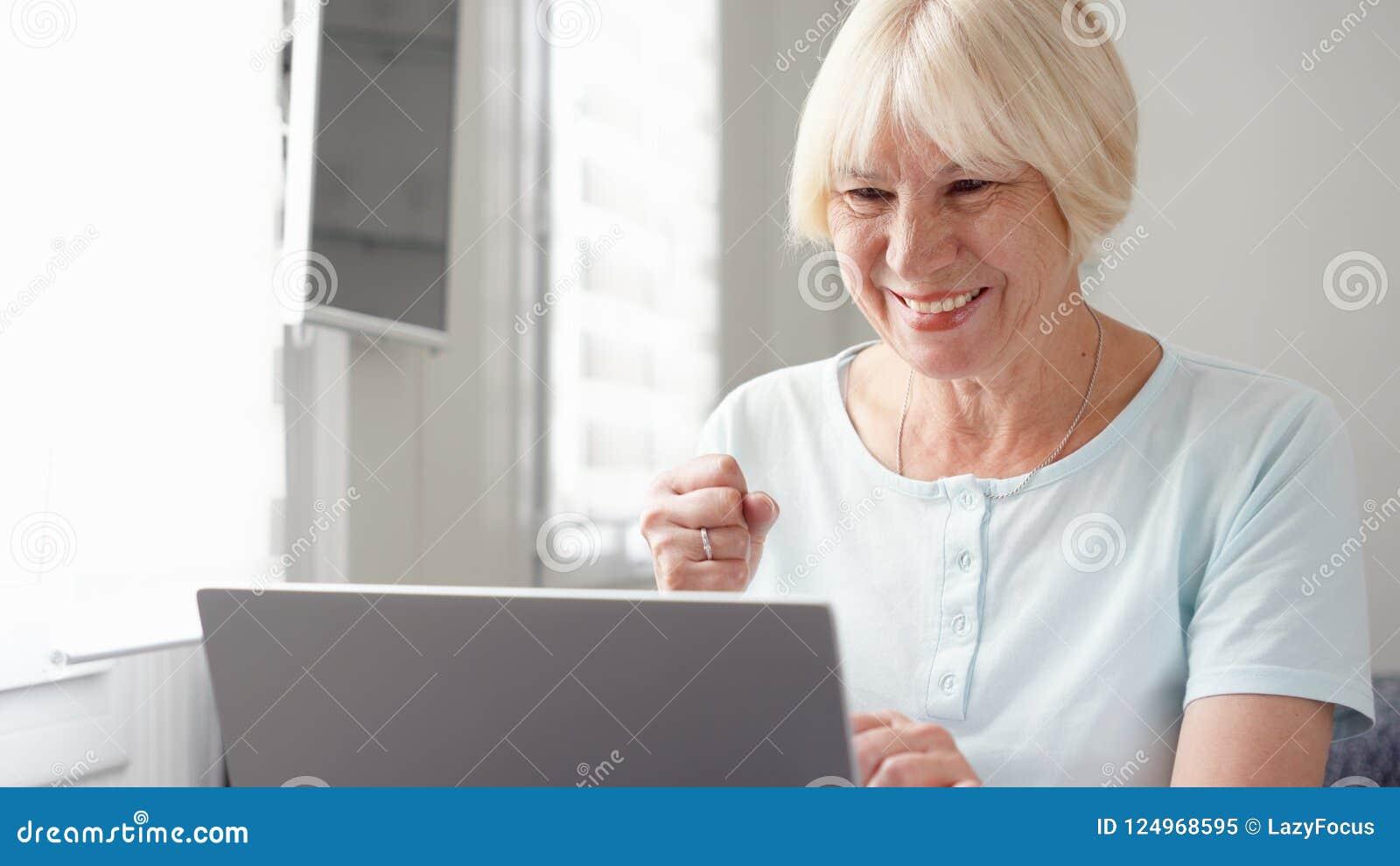 Äldre hög blond kvinna som hemma arbetar på bärbar datordatoren Lyckliga mottagna goda nyheter som är upphetsade och
