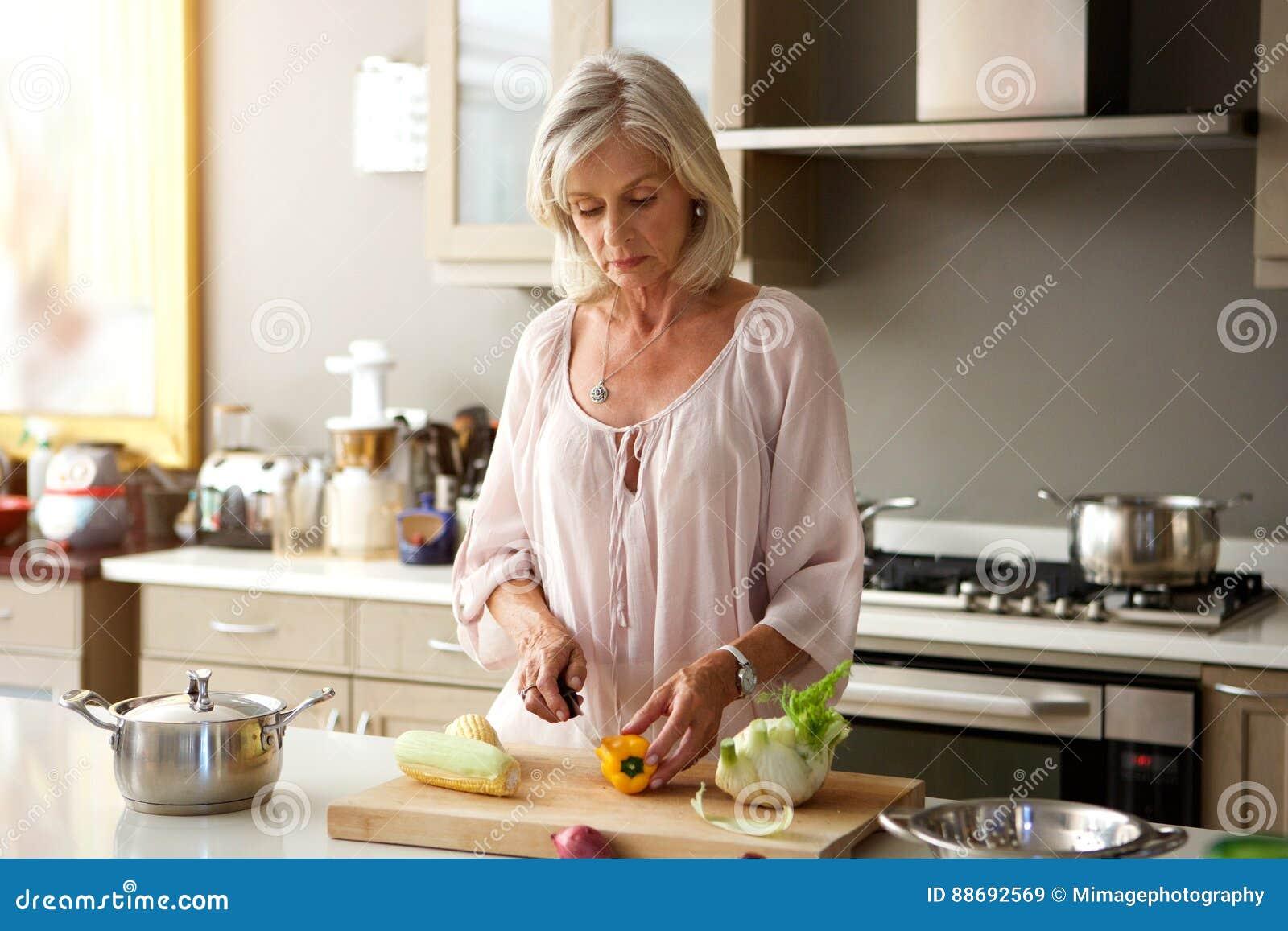 Äldre kvinna i kök som förbereder sunt mål