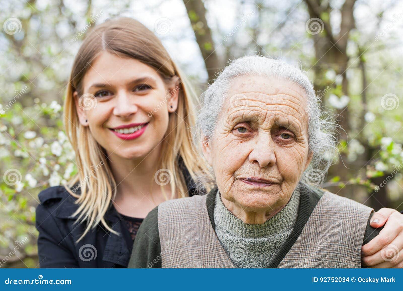 Äldre kvinna med hennes utomhus- vårdare
