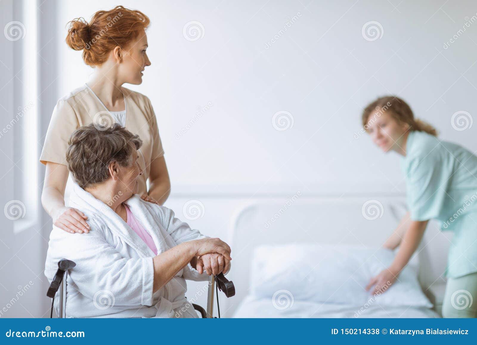 Äldre kvinna på rullstolen i vårdhem med den hjälpsamma doktorn på hennes sida och unga sjuksköterska som gör sängen