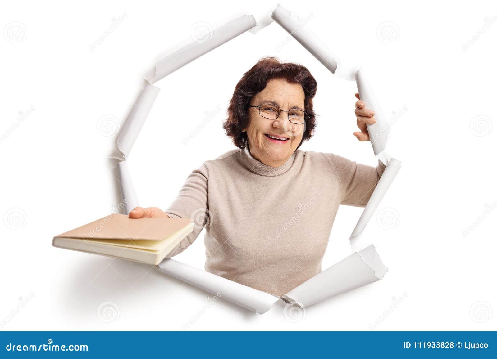 Äldre kvinna som bryter till och med papper