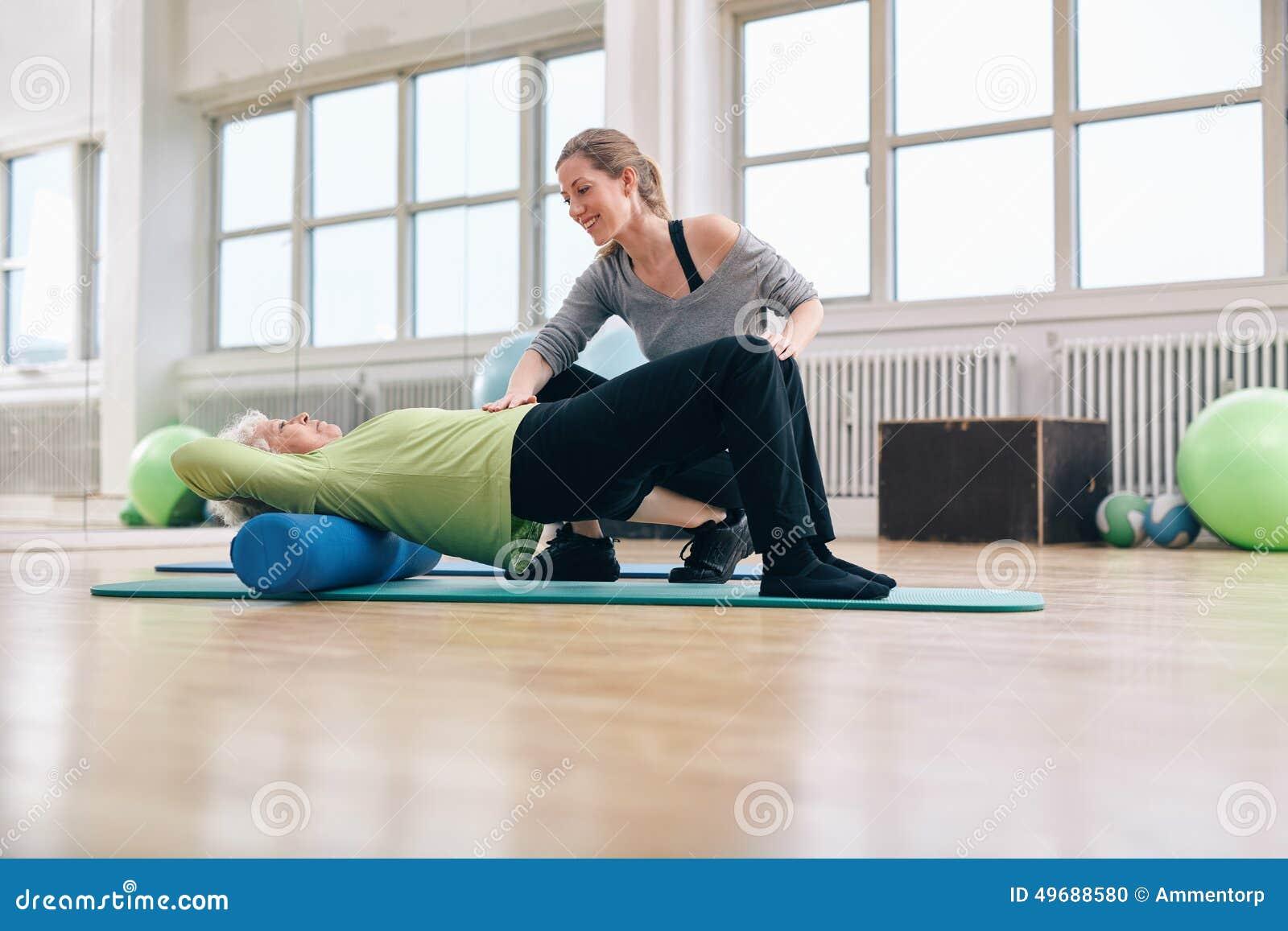 Äldre kvinna som gör pilatesgenomkörare med den personliga instruktören