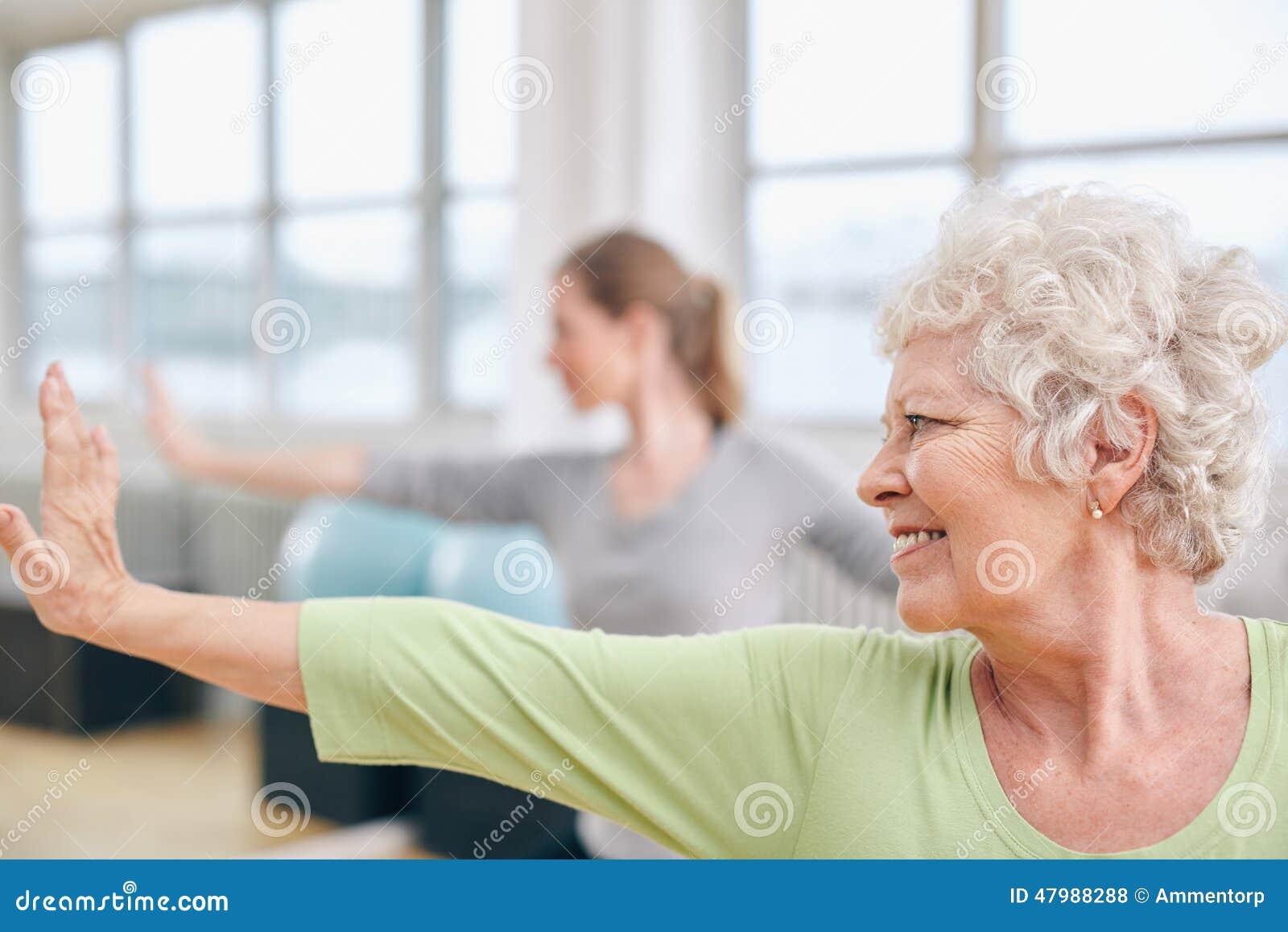 Äldre kvinna som gör sträcka genomkörare på yogagrupp