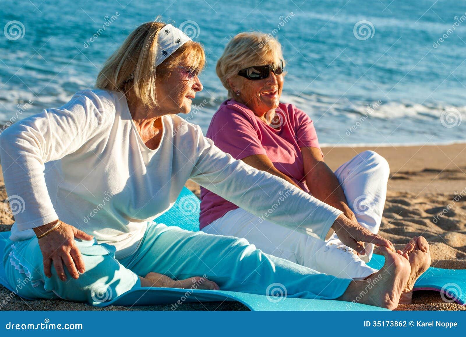 Äldre kvinnor som gör sträckning, övar på stranden.