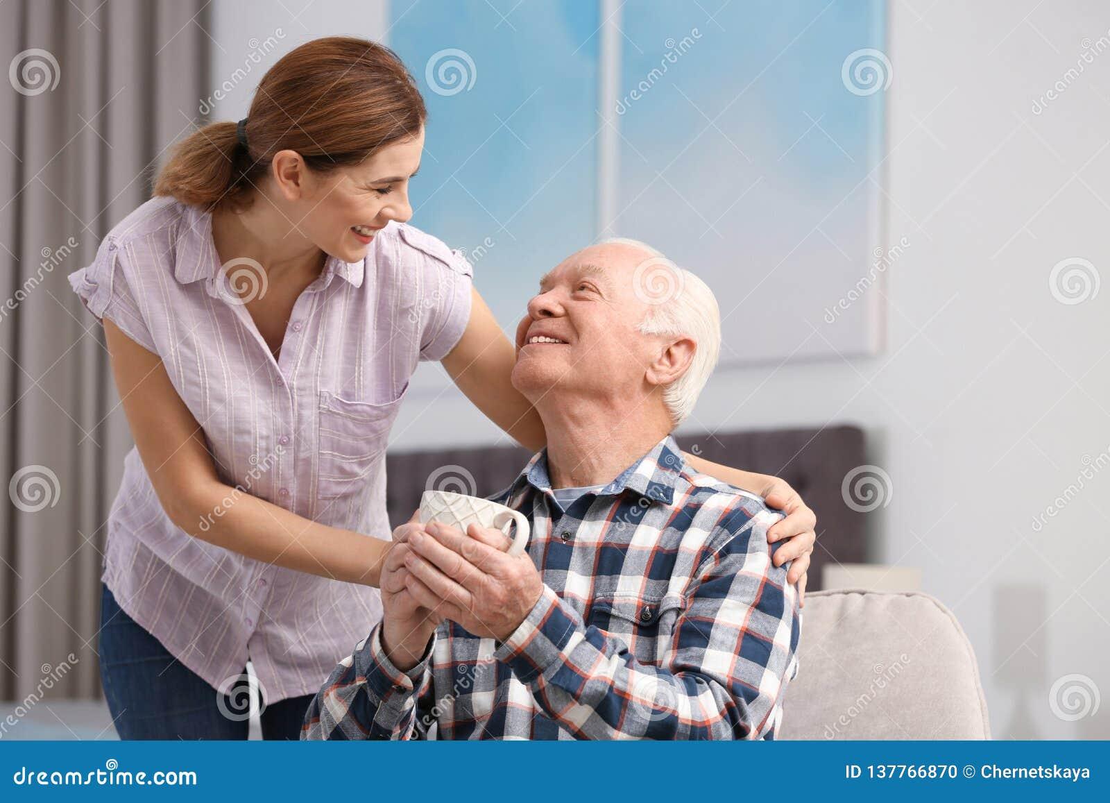 Äldre man med kopp te nära kvinnlig anhörigvårdare hemma