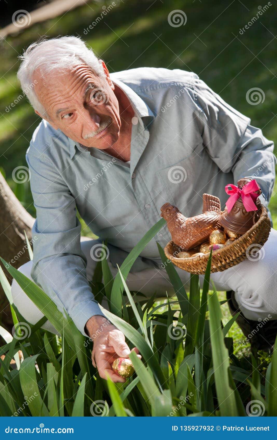 Äldre man som döljer easter ägg