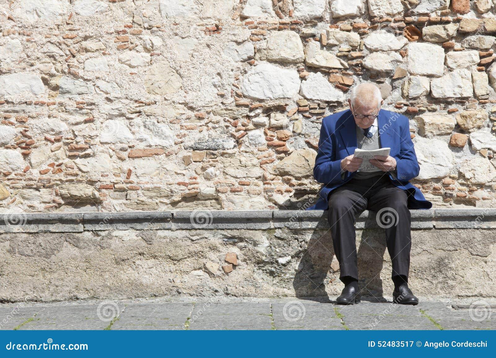 Äldre manläsning och sammanträde på en stenbänk Stenvägg