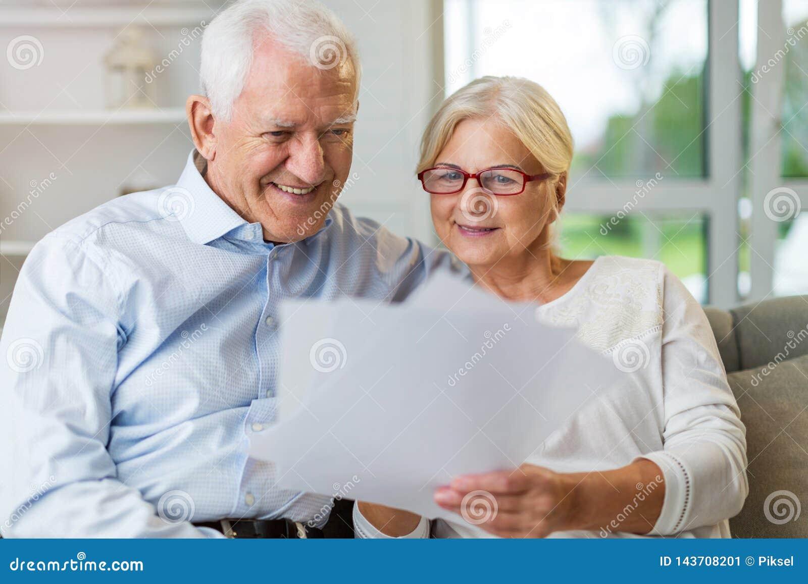 Äldre parläsninglegitimationshandlingar tillsammans på soffan