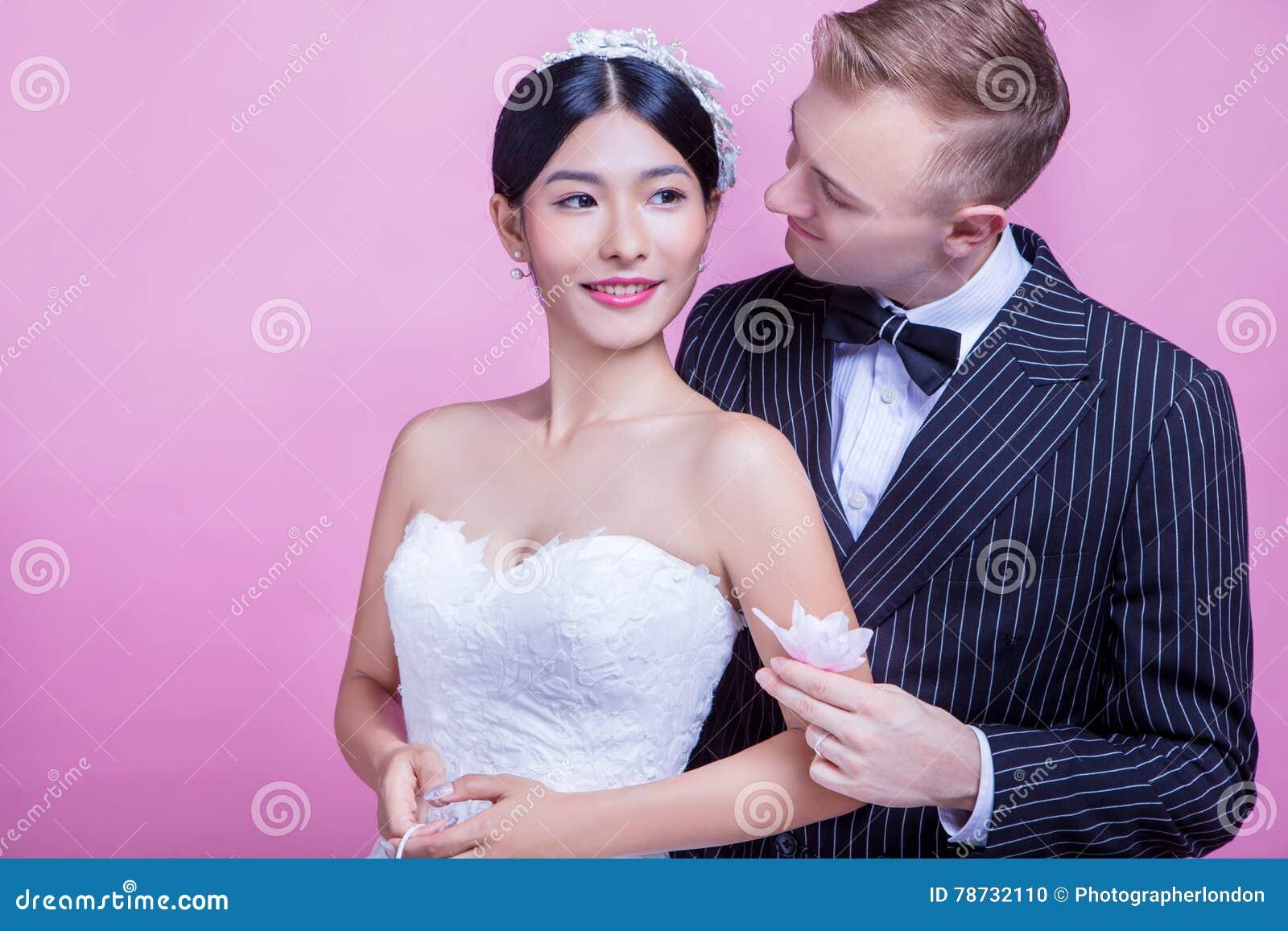 Älska brudguminnehavet blomma, medan se bruden mot rosa bakgrund