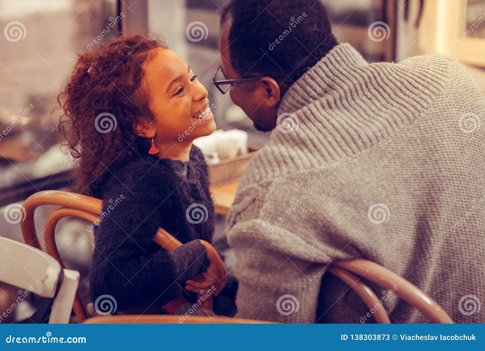 Älska denhaired fadern som ser hans gulliga älskvärda dotter