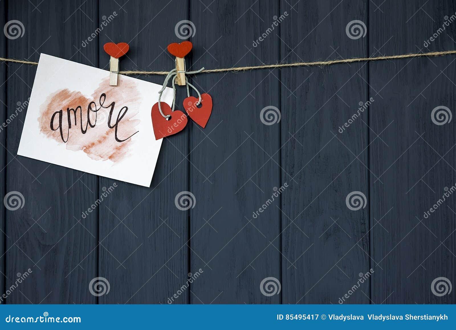 Älska för Amore för ` för kortet för valentin` s naturlig kabel ` och rött ben som hänger på lantlig drivvedtexturbakgrund, kopie