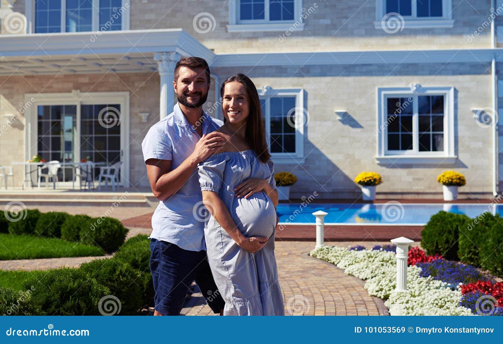 Älska maken och den gravida frun som framme poserar av nytt modernt H