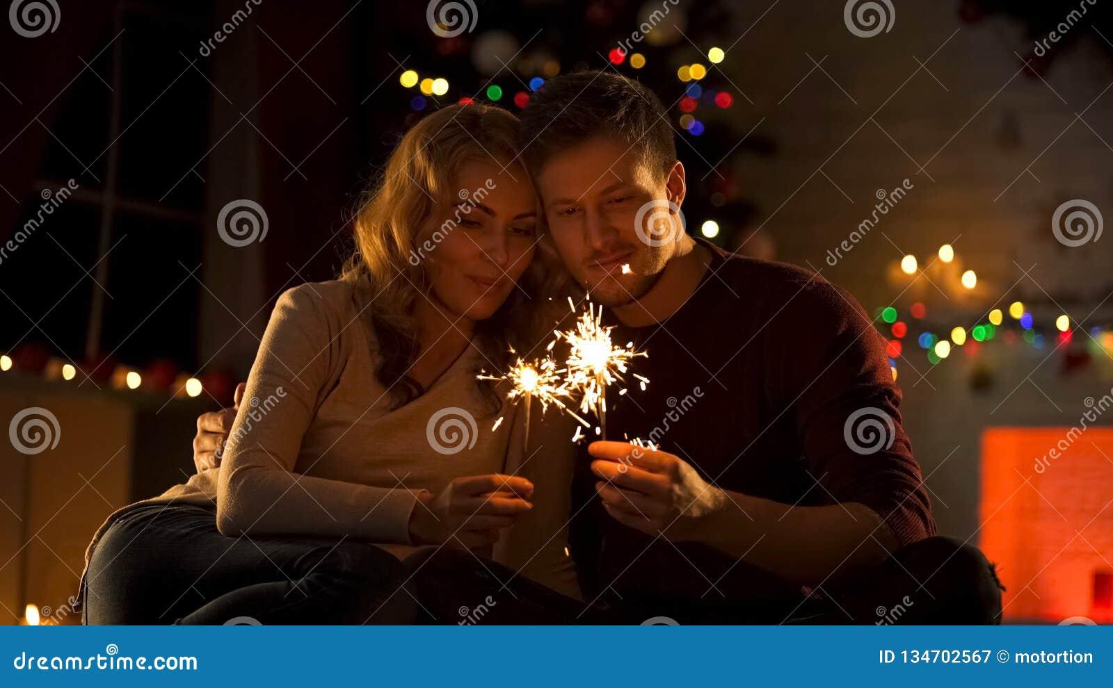 Älska par med Bengal ljus som sitter nära Xmas-trädet som gör önska i nytt år