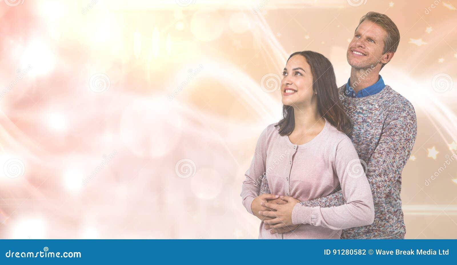 Älska par som ler, medan se bort över suddighetsbakgrund