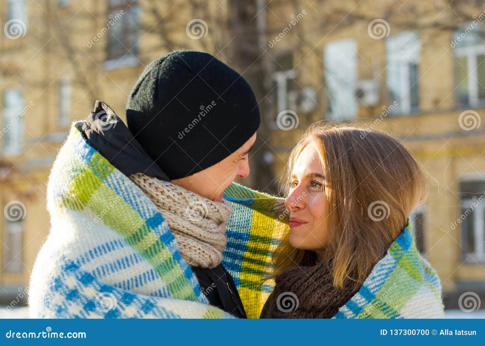 Älska par som ser de och att skratta plädet i vinter Grabben kramar en flicka på gatan i vinter