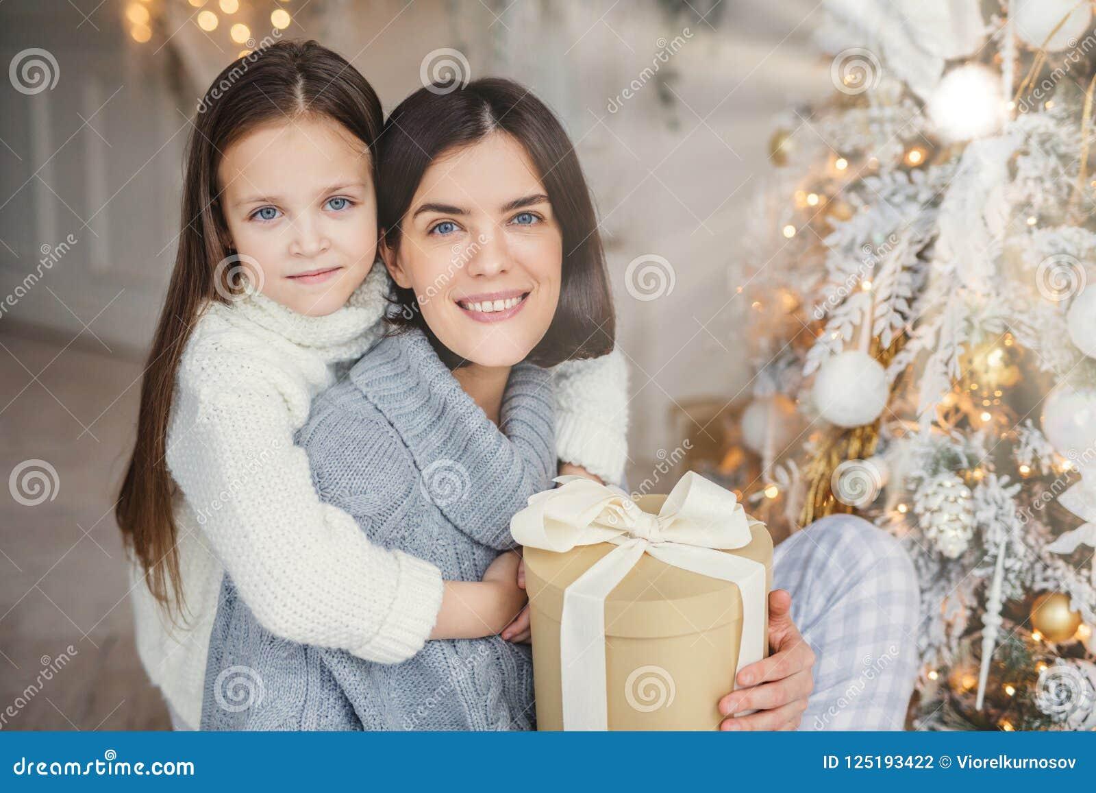 Älskar förtjusande blått synade små ungehuggs med stort hennes moder, som rymmer den slågna in gåvaasken, trädet för det nya året