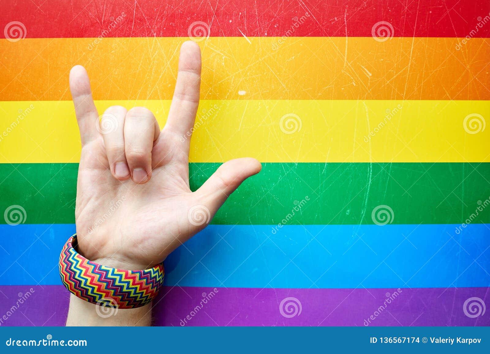 'Älskar jag dig 'i språket för det amerikanska tecknet ASL som visar en mans hand på bakgrunden av flaggan av gemenskap för LGBT