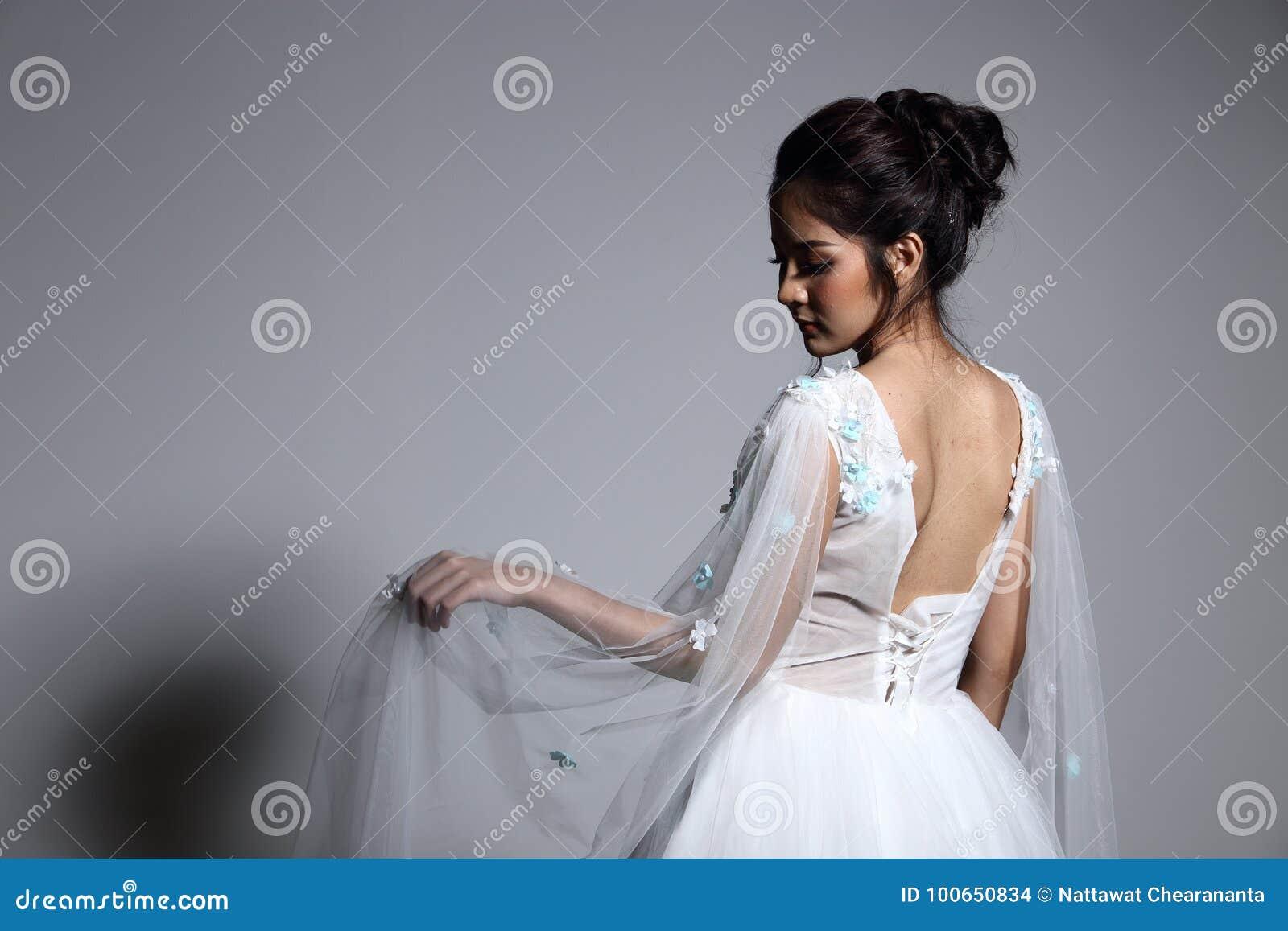 Älskvärd asiatisk härlig kvinnabrud i vit klänning w för bröllopkappa