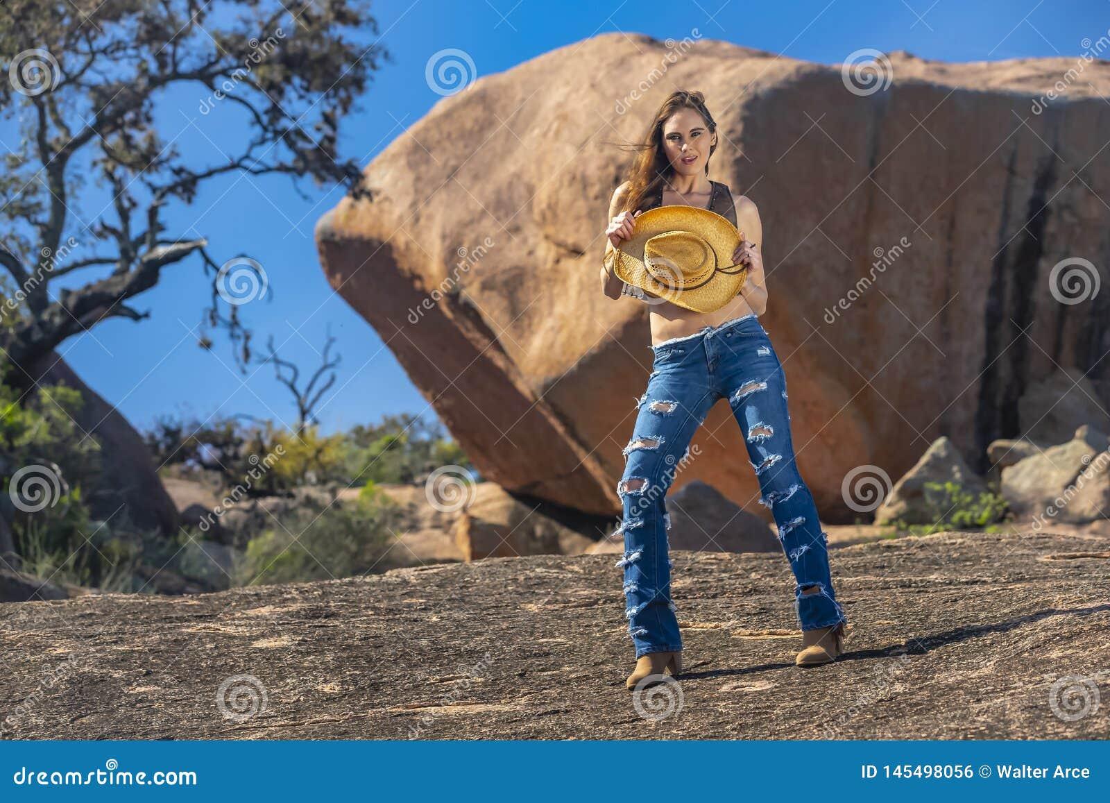 Älskvärd brunettcowgirlmodell Posing Outdoors