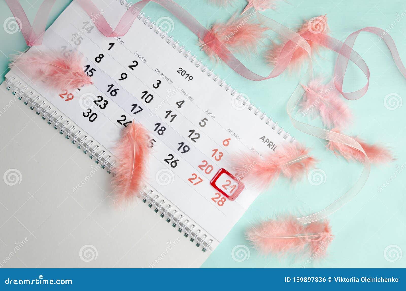 Älskvärd enkel orientering av kalendern av April, fjädrar och det rosa bandet Top beskådar Begrepp av påskferie