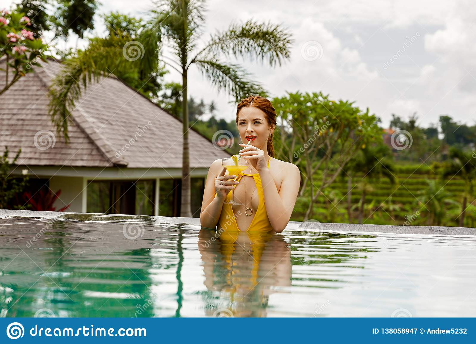Älskvärd flicka i en gul baddräkt i simbassängen