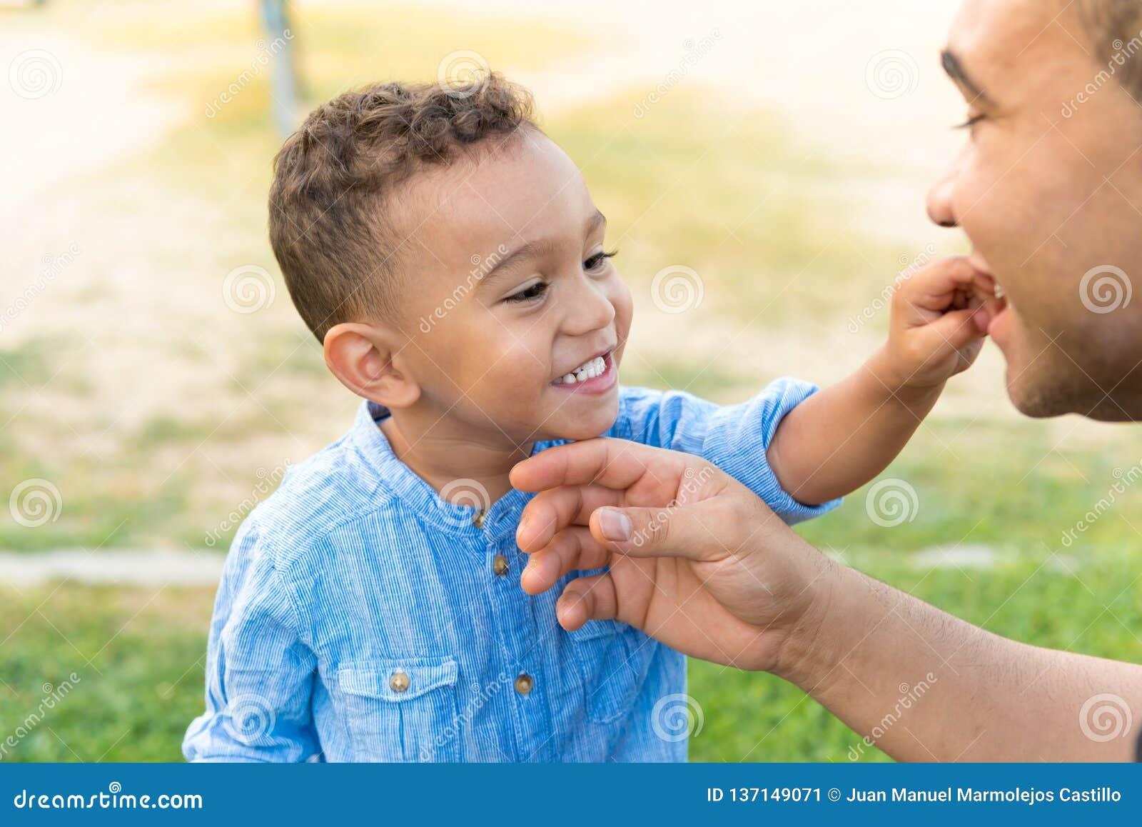 Älskvärd unge som visar tänder till hans fader