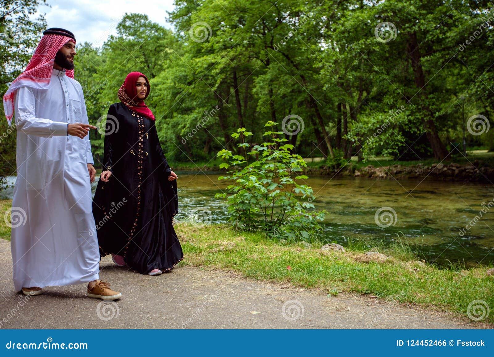 Älskvärda arabiska par i traditionell kläder som utomhus omfamnar
