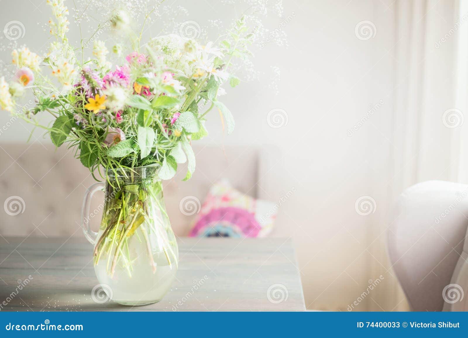 Älskvärda lösa blommor samlar ihop i den glass vasen på tabellen i ljus vardagsrum, hem- garnering