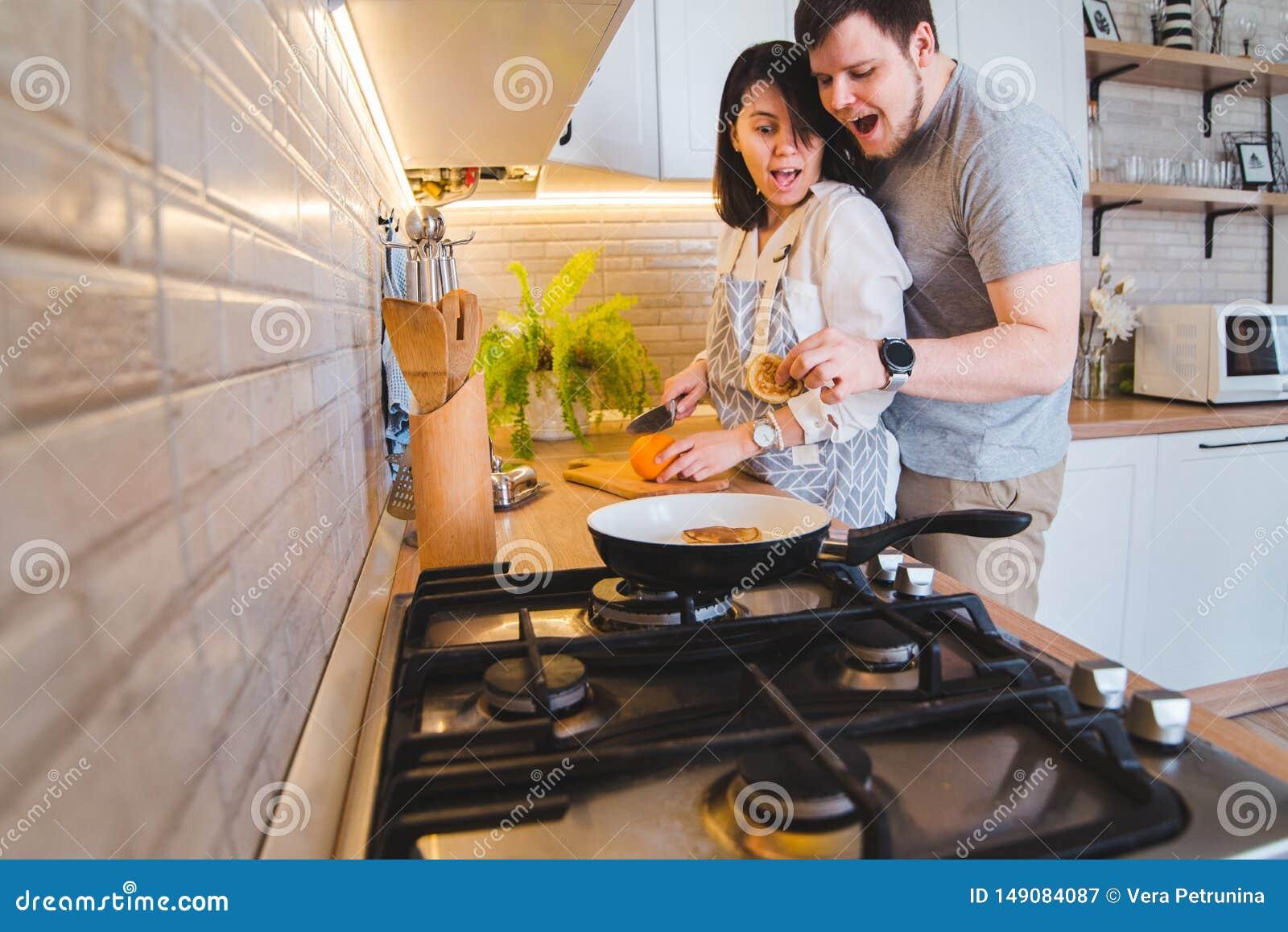 Älskvärda par som kramar på köket, medan laga mat frukosten