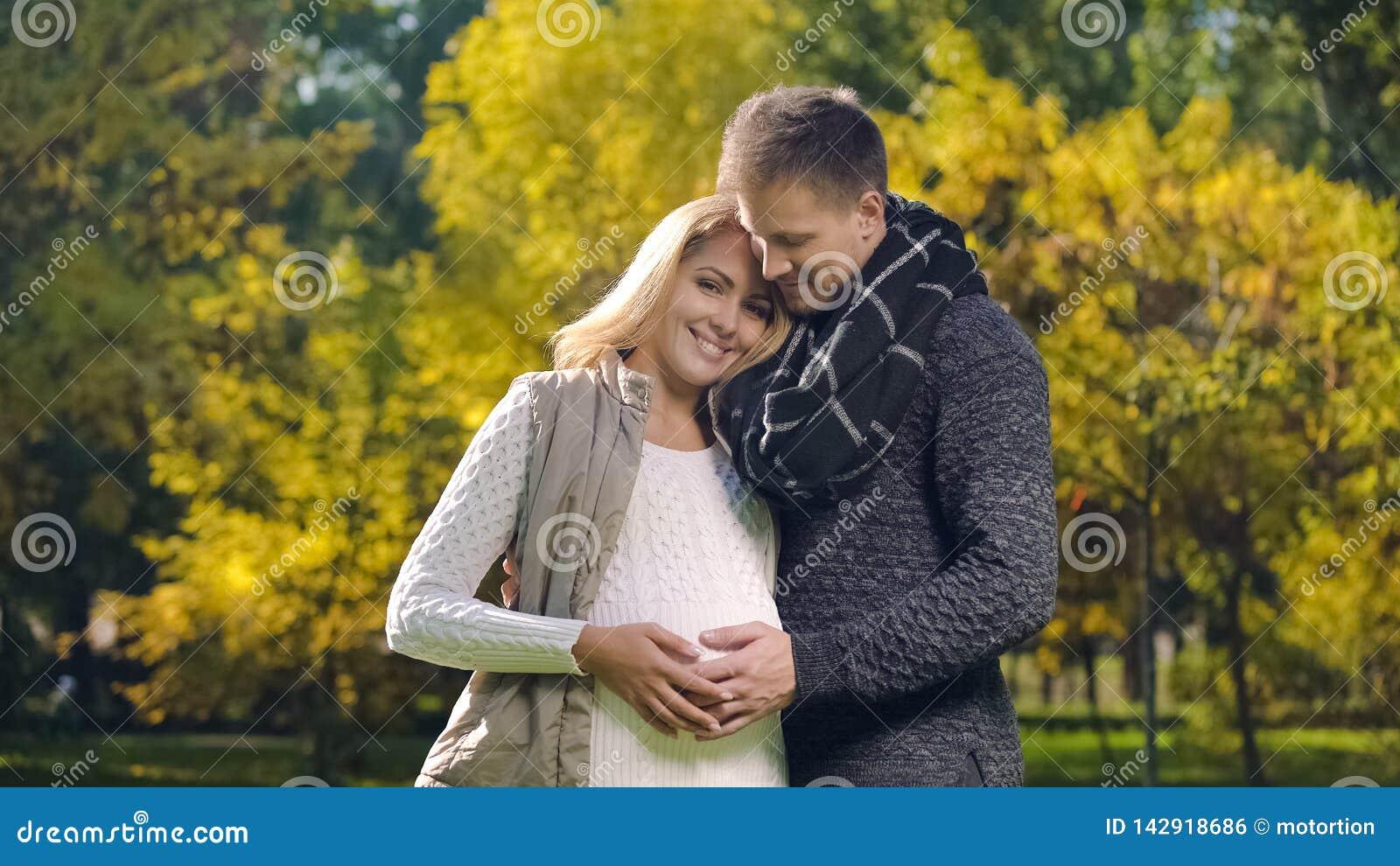 Älskvärda par som trycker på den gravida magen, medicinsk klinik för moderskapomsorgvälfärd