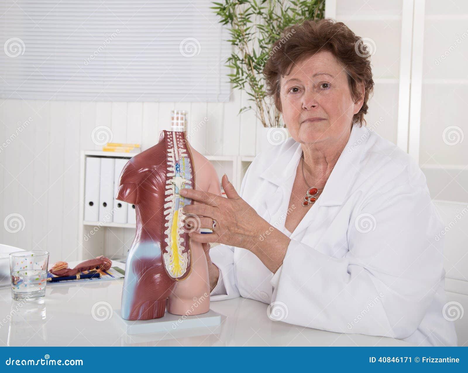 Ältere Ärztin, die den menschlichen Körper mit dem Torso erklärt