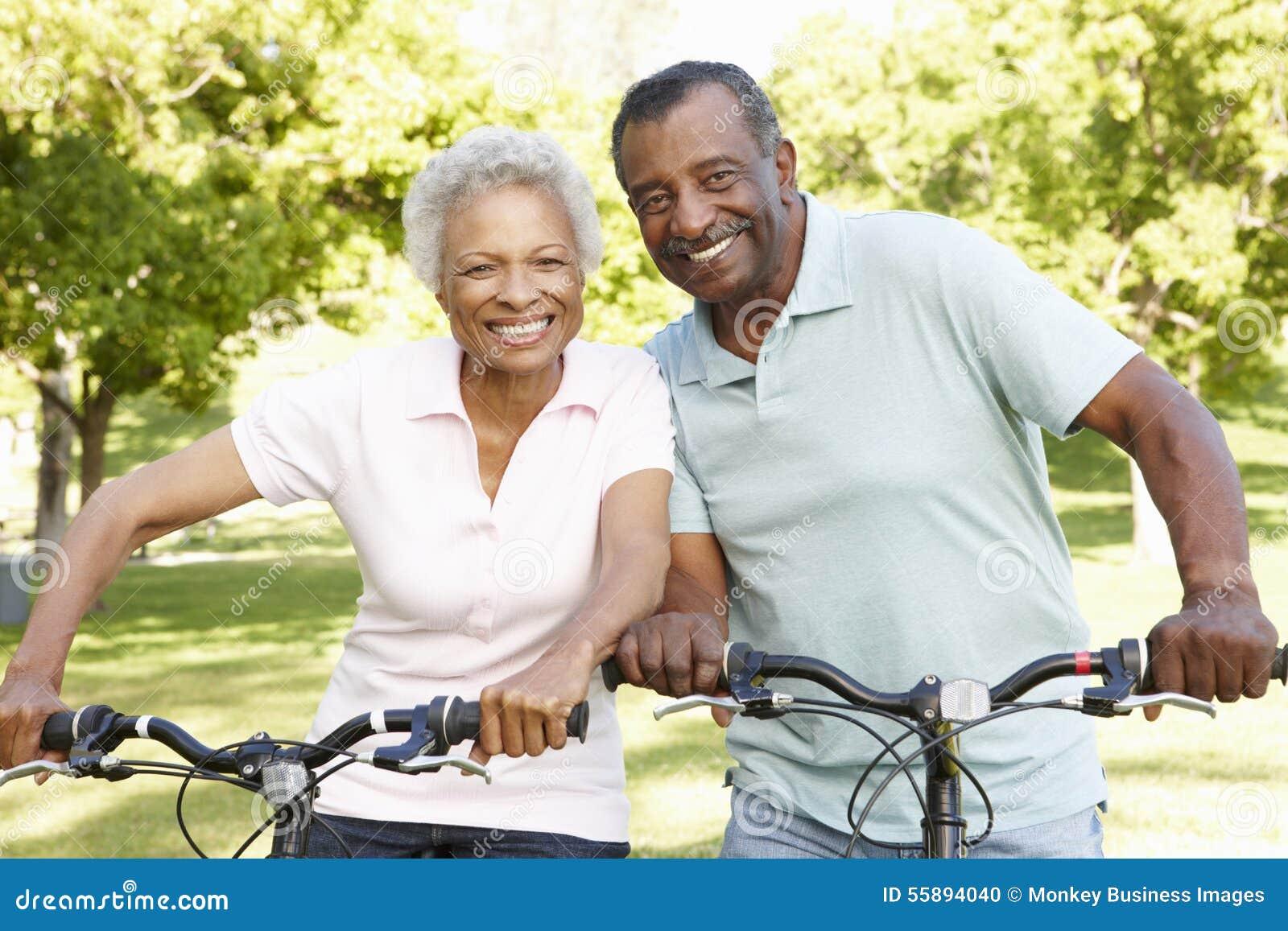 Ältere Afroamerikaner-Paare, die in Park radfahren