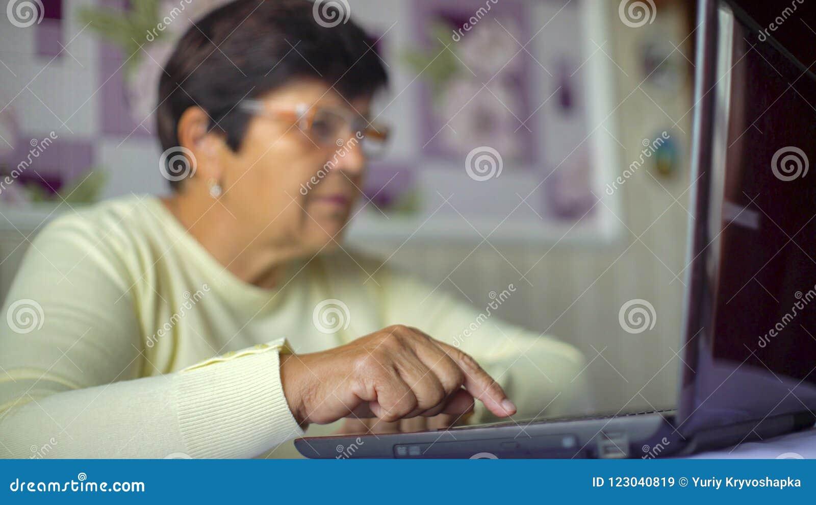 Ältere alte Frau in den Brillen, die zu Hause Internet auf Laptop mit freiem Raum und Kopienraum surfen