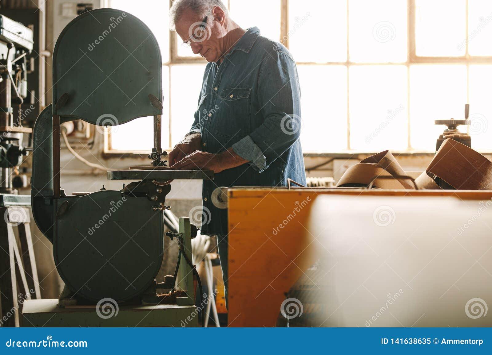 Ältere Arbeitskraft, die an Bandsägemaschine arbeitet