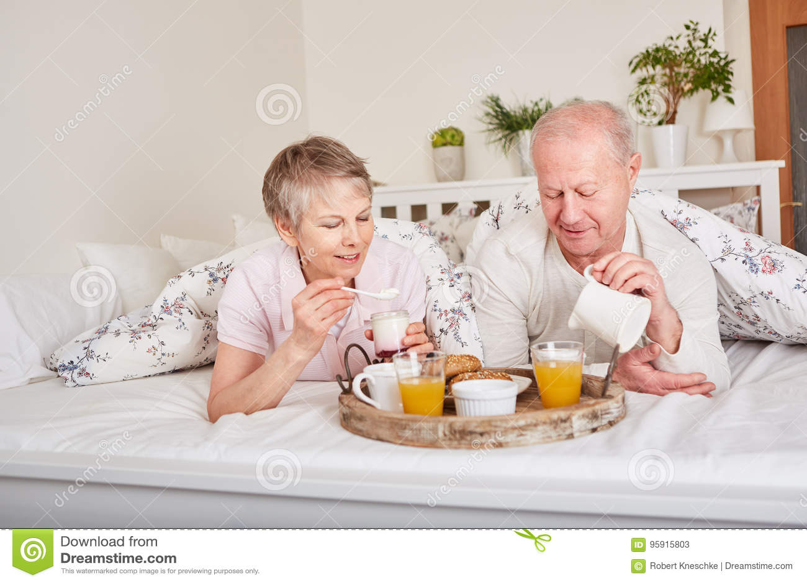 Ältere Bürger, die im Bett frühstücken