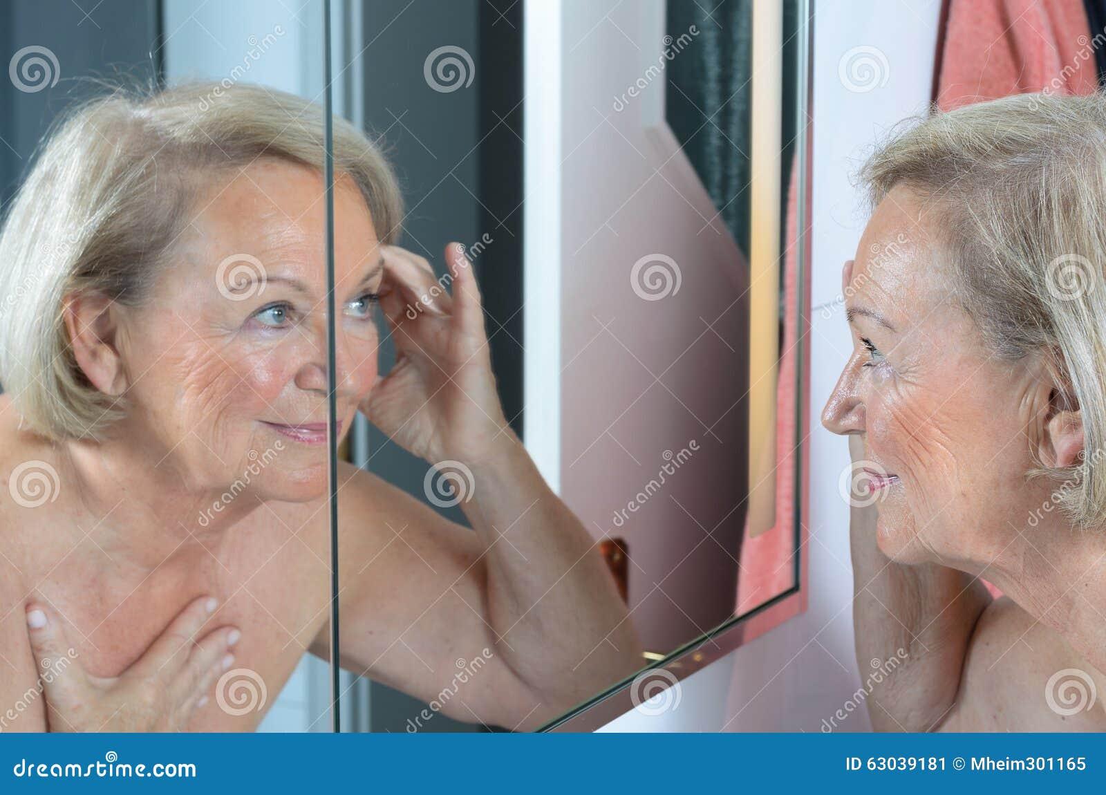 Ältere Dame, die ihre Haut im Spiegel überprüft