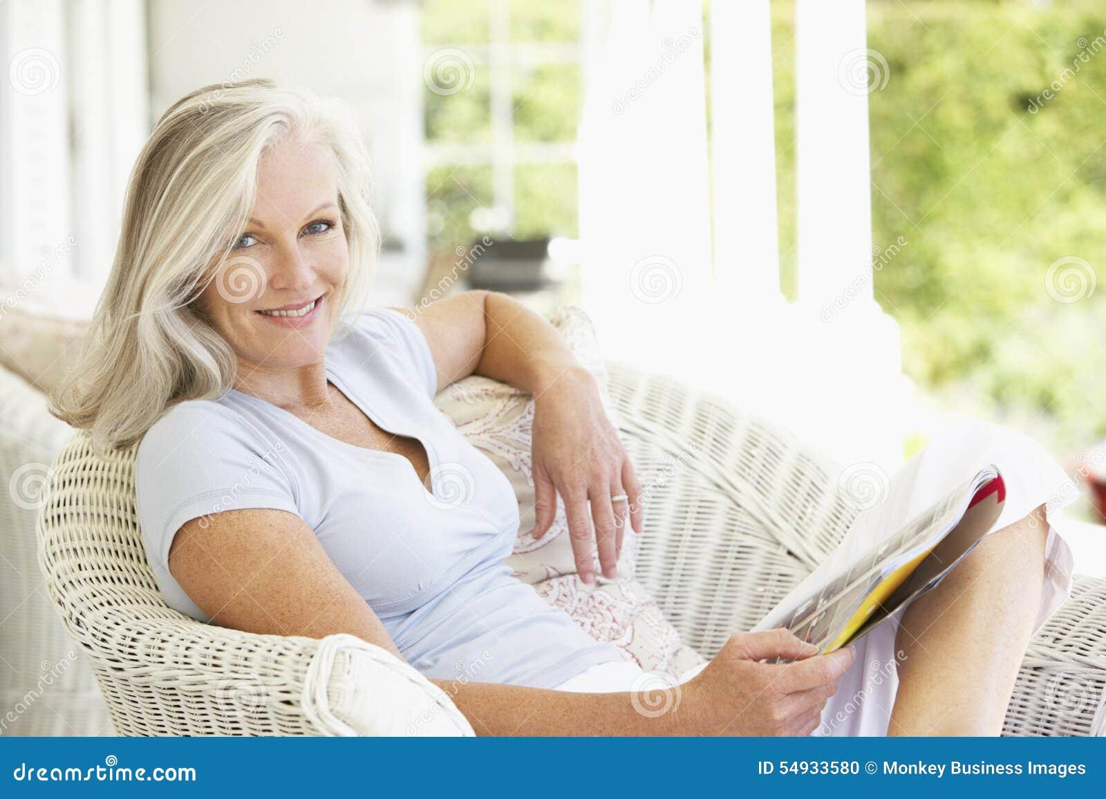 Ältere Frau, die außerhalb der Lesezeitschrift sitzt