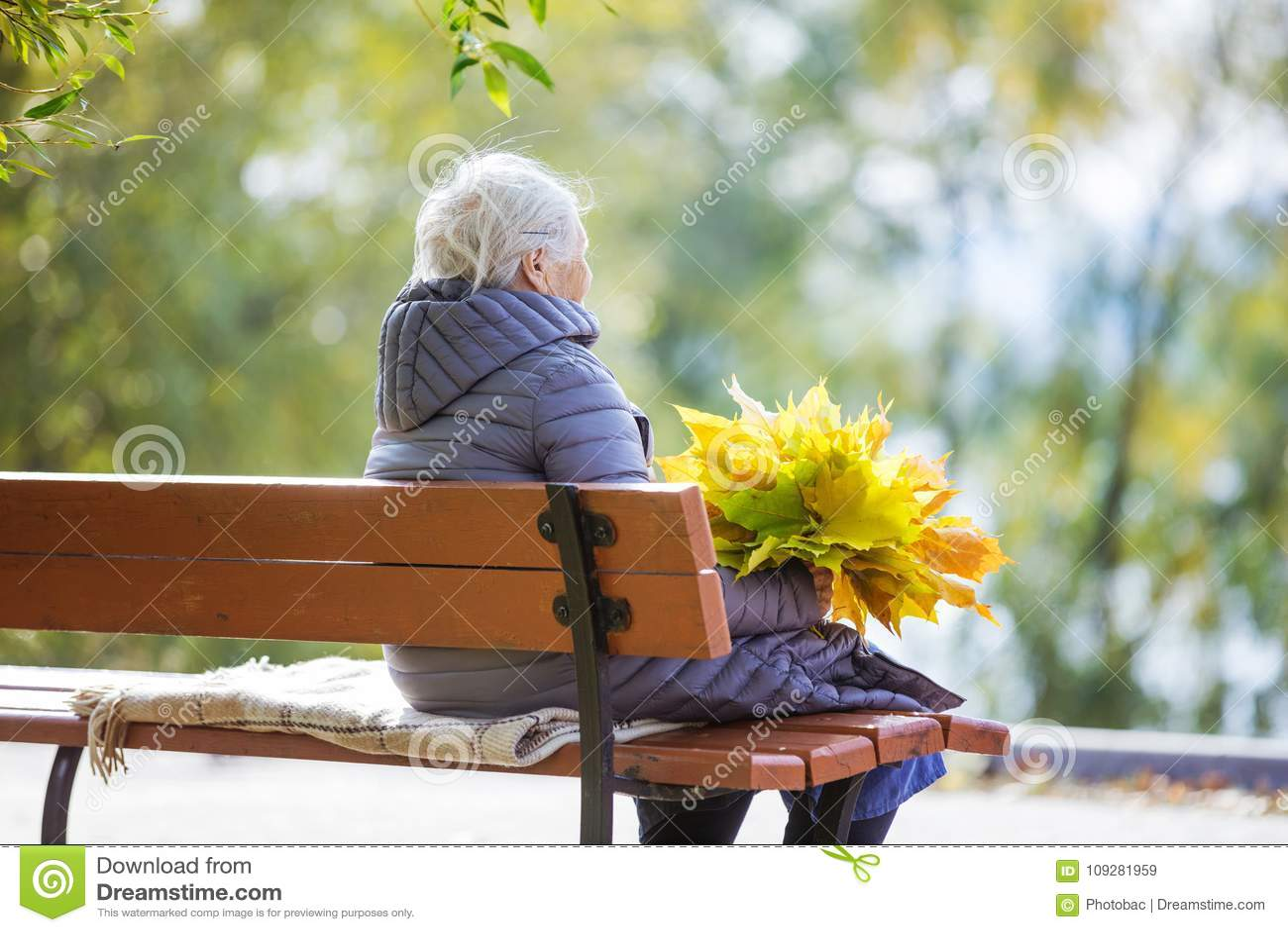 Ältere Frau, die auf Bank im Park sitzt