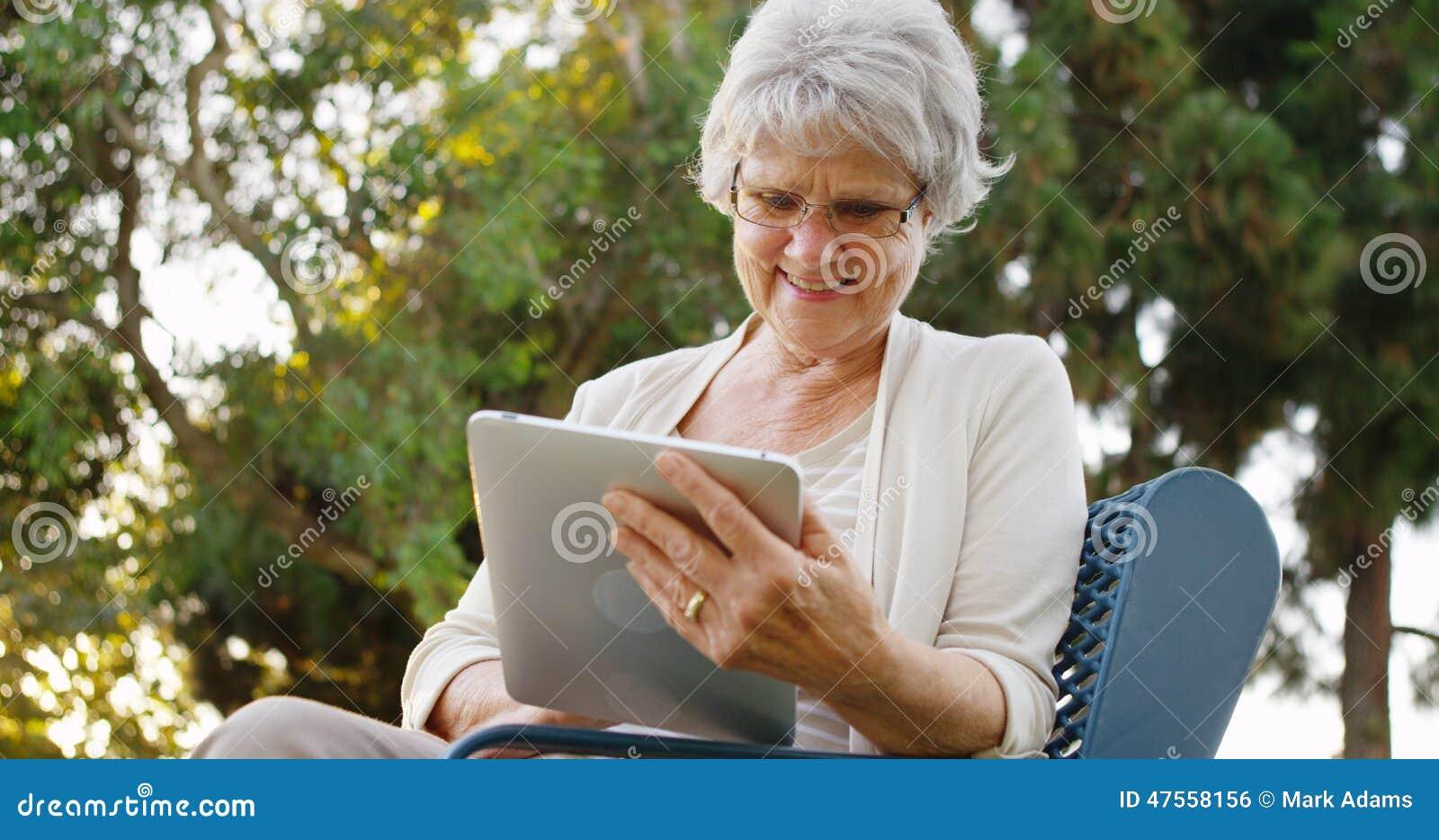 Ältere Frau, die glücklich das Netz auf Tablette surft