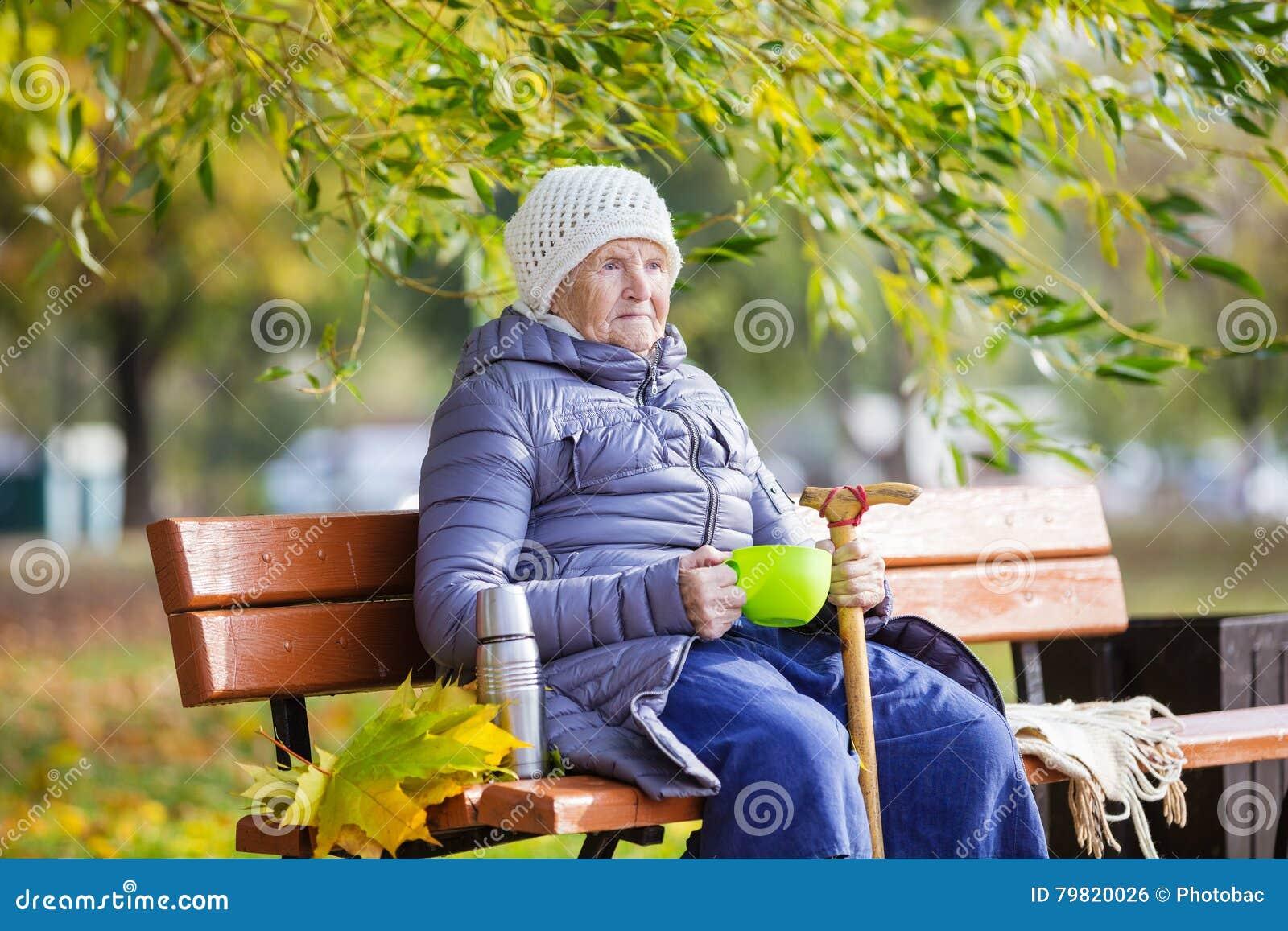 Ältere Frau, die heißen Tee im Park trinkt