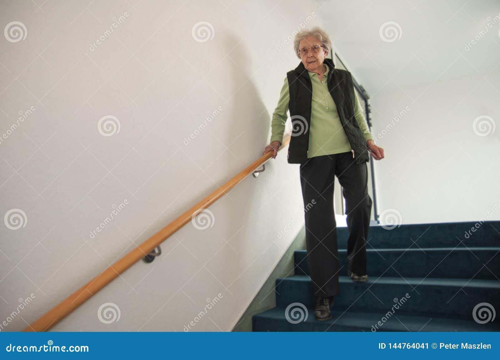 Ältere Frau, die hinunter die Treppe geht
